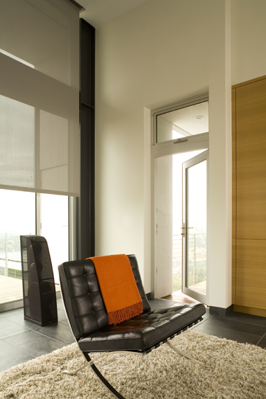 The orange throw creates a spot of color in an otherwise muted palette, creating a visual anchor. Design: LeanArch. Photo: Claudio Santini