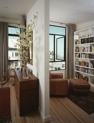 "A partial wall divides the bedroom from the library. Karin Payson used larger windows in her library, where privacy was not as much of a concern as in the bedroom areas. The partial wall lets the bedroom ""borrow"" light from the living room."