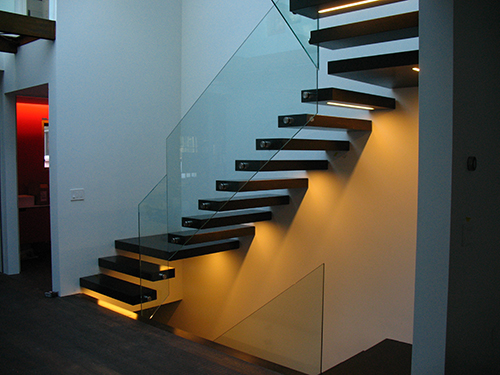The completed stair with wood-clad steel treads and glass panel rails. LED lights illuminate the underside of the stair with a warm glow that complements the cooler daylighting coming from the skylight above. Image: Mark English Architects