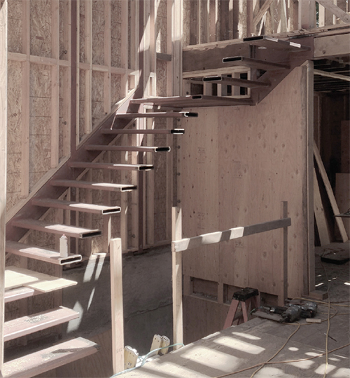 Construction photo showing the stair landings and clockwise ascent as seen from the main floor. The steel treads are welded to a frame that runs along the back wall. Image: Mark English Architects