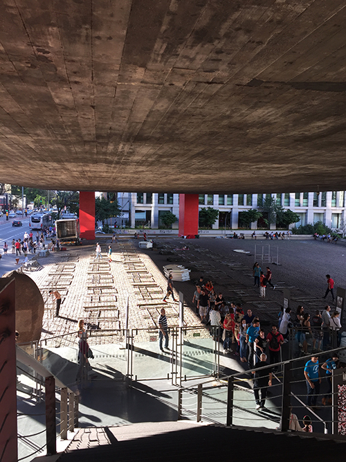 São Paulo Museum of Art (MASP), designed by architect Lina Bo Bardi. Visitors enter the museum by ascending exterior stairs at either end of the building. Below, an open-air market makes use of the public space shaded by the suspended building. Image: Mark English Architects.